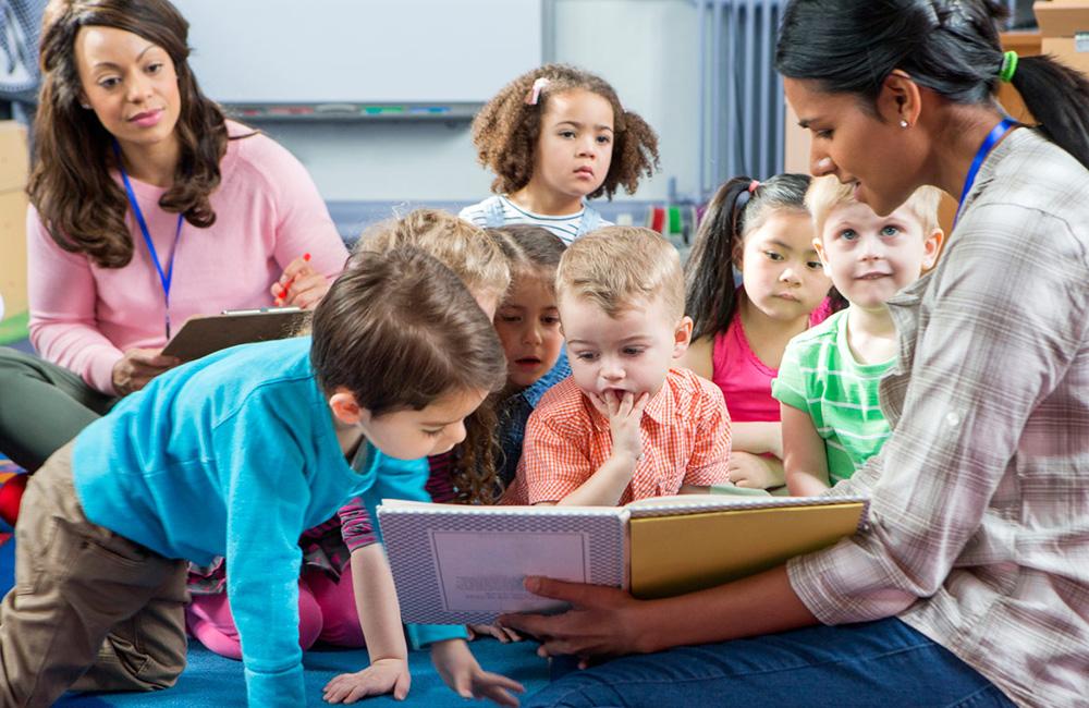 children reading the Kindness Curriculum from a teacher's book