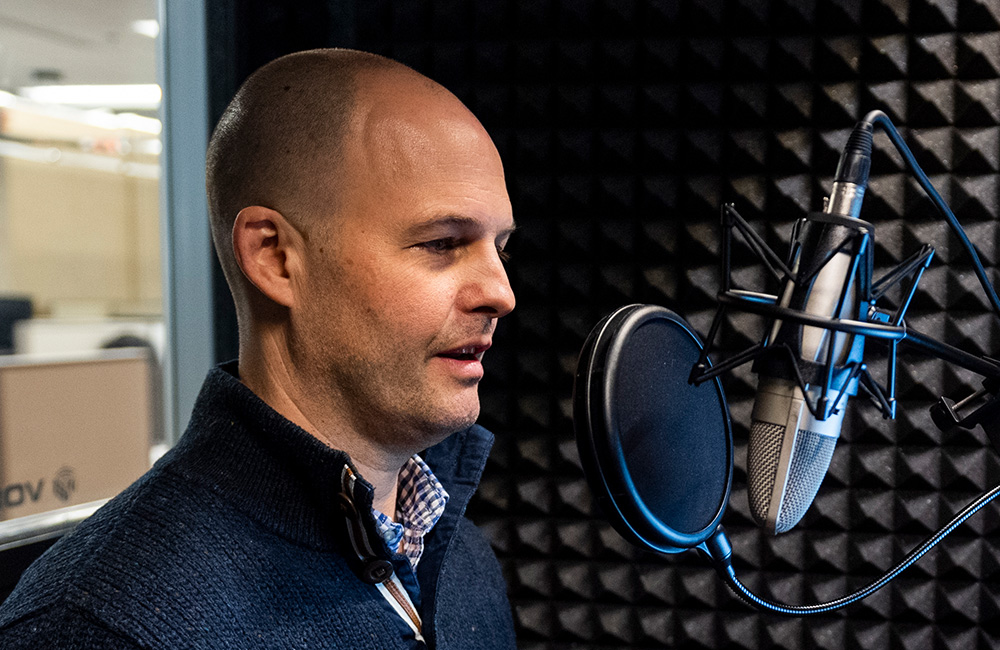 Dr. Cortland Dahl speaking into a microphone in a recording booth